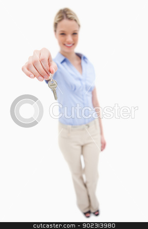 Smiling woman handing over key stock photo, Smiling woman handing over key against a white background by Wavebreak Media