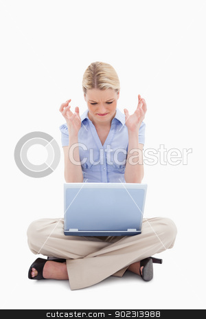 Woman sitting and angry about her laptop stock photo, Woman sitting and angry about her laptop against a white background by Wavebreak Media