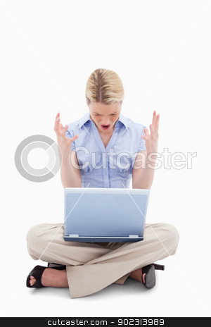 Sitting woman yelling at her laptop stock photo, Sitting woman yelling at her laptop against a white background by Wavebreak Media