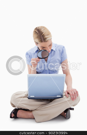Woman using magnifier to look at her laptop stock photo, Woman using magnifier to look at her laptop against a white background by Wavebreak Media