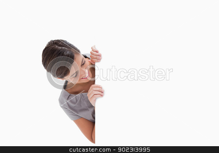 Woman looking around the corner stock photo, Woman looking around the corner against a white background by Wavebreak Media