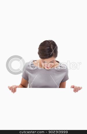 Woman looking down on blank wall stock photo, Woman looking down on blank wall against a white background by Wavebreak Media