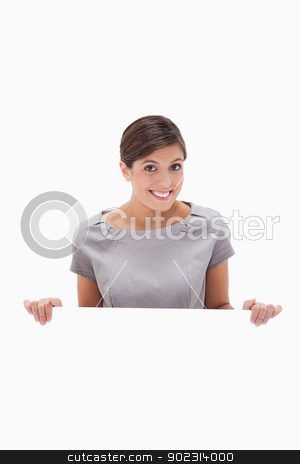 Smiling woman looking over blank wall stock photo, Smiling woman looking over blank wall against a white background by Wavebreak Media