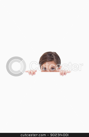 Sneaky woman looking over blank wall stock photo, Sneaky woman looking over blank wall against a white background by Wavebreak Media