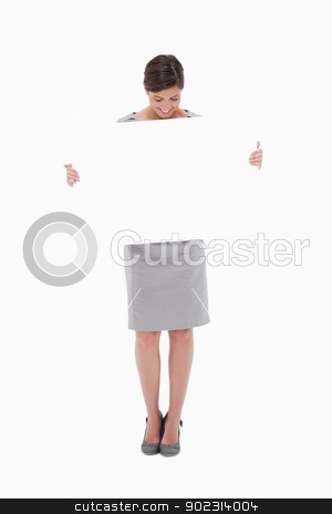 Woman looking down at blank sign in her hands stock photo, Woman looking down at blank sign in her hands against a white background by Wavebreak Media