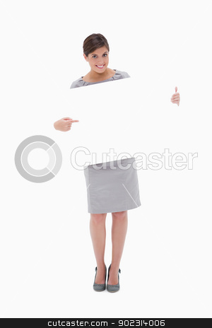 Smiling woman pointing at blank sign in her hands stock photo, Smiling woman pointing at blank sign in her hands against a white background by Wavebreak Media