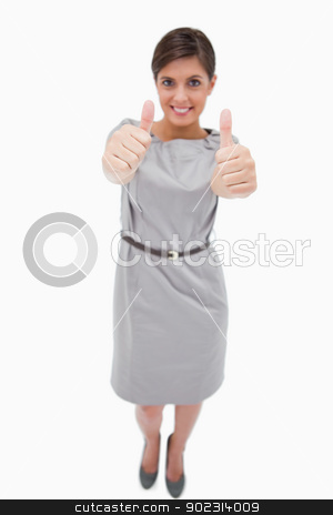 Smiling woman giving thumbs up stock photo, Smiling woman giving thumbs up against a white background by Wavebreak Media