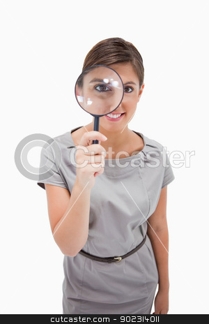 Woman using magnifier stock photo, Woman using magnifier against a white background by Wavebreak Media