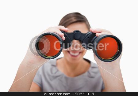 Woman looking through spyglasses stock photo, Woman looking through spyglasses against a white background by Wavebreak Media