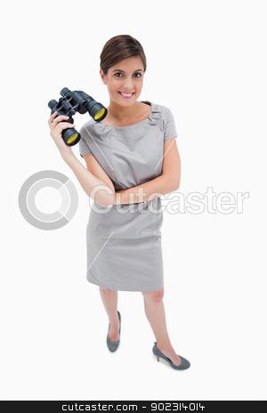 Woman standing with binoculars stock photo, Woman standing with binoculars against a white background by Wavebreak Media