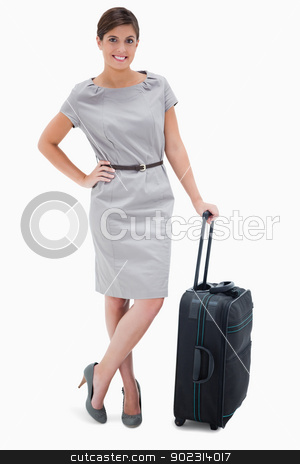 Woman standing next to wheely bag stock photo, Woman standing next to wheely bag against a white background by Wavebreak Media