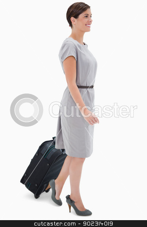 Side view of woman with wheely bag stock photo, Side view of woman with wheely bag against a white background by Wavebreak Media