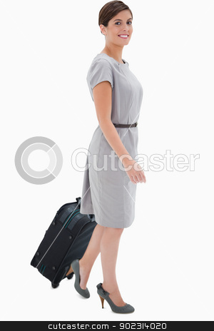 Side view of smiling woman with wheely bag stock photo, Side view of smiling woman with wheely bag against a white background by Wavebreak Media