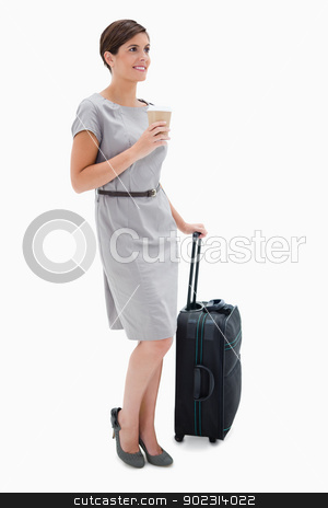 Side view of woman with coffee and wheely bag stock photo, Side view of woman with coffee and wheely bag against a white background by Wavebreak Media