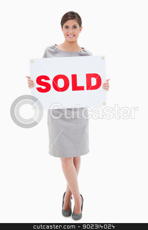 Woman holding sold sign stock photo, Woman holding sold sign against a white background by Wavebreak Media