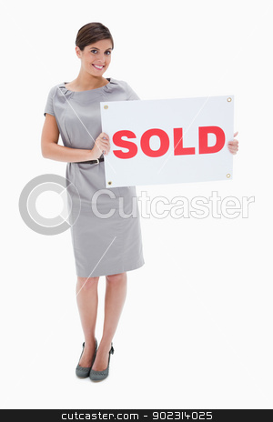 Woman holding sold sign in her hands stock photo, Woman holding sold sign in her hands against a white background by Wavebreak Media