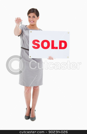 Woman with sold sign handing over key stock photo, Woman with sold sign handing over key against a white background by Wavebreak Media
