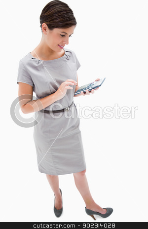 Side view of woman with hand calculator stock photo, Side view of woman with hand calculator against a white background by Wavebreak Media