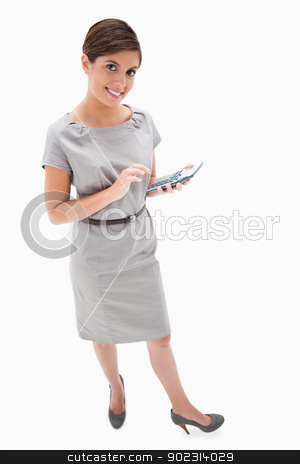 Smiling woman with hand calculator stock photo, Smiling woman with hand calculator against a white background by Wavebreak Media