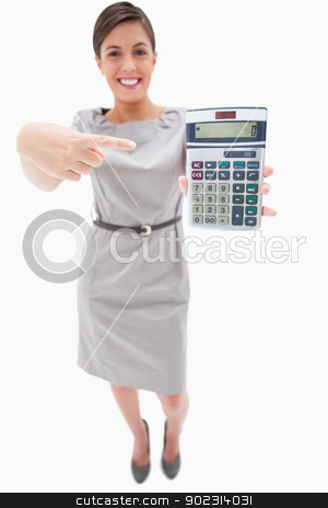 Woman pointing at hand calculator stock photo, Woman pointing at hand calculator against a white background by Wavebreak Media