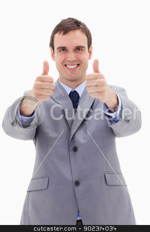 Smiling businessman giving thumbs up stock photo, Smiling businessman giving thumbs up against a white background by Wavebreak Media