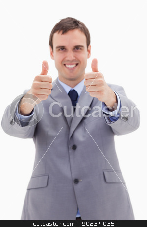 Thumbs up given by smiling businessman stock photo, Thumbs up given by smiling businessman against a white background by Wavebreak Media