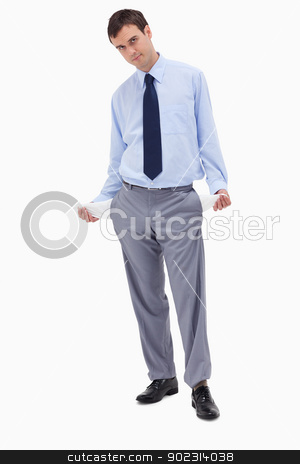Businessman showing his empty pockets stock photo, Businessman showing his empty pockets against a white background by Wavebreak Media
