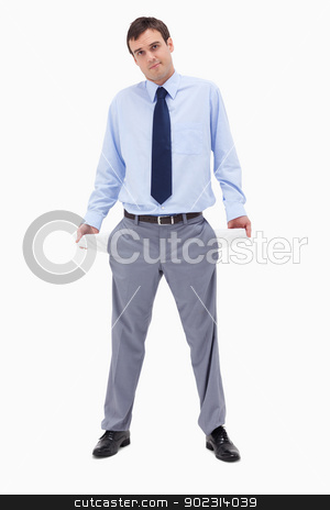 Broke businessman showing his empty pockets stock photo, Broke businessman showing his empty pockets against a white background by Wavebreak Media