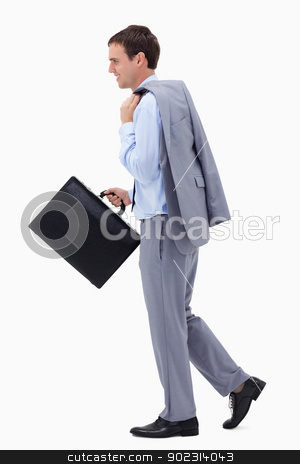 Side view of walking and smiling businessman with suitcase stock photo, Side view of walking and smiling businessman with suitcase against a white background by Wavebreak Media