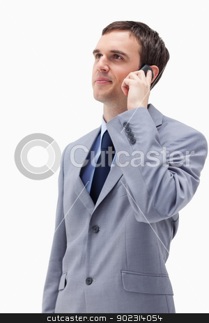 Businessman looking up while on the phone stock photo, Businessman looking up while on the phone against a white background by Wavebreak Media