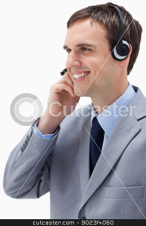 Side view of businessman using headset stock photo, Side view of businessman using headset against a white background by Wavebreak Media