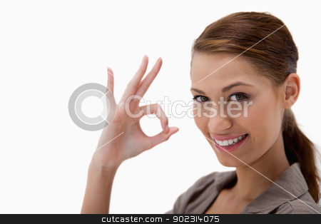 Side view of woman giving approval stock photo, Side view of woman giving approval against a white background by Wavebreak Media