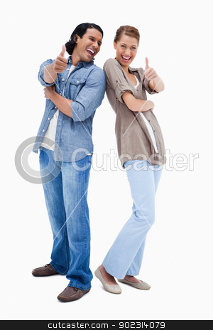 Smiling young couple giving thumbs up stock photo, Smiling young couple giving thumbs up against a white background by Wavebreak Media