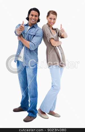 Smiling couple giving thumbs up stock photo, Smiling couple giving thumbs up against a white background by Wavebreak Media