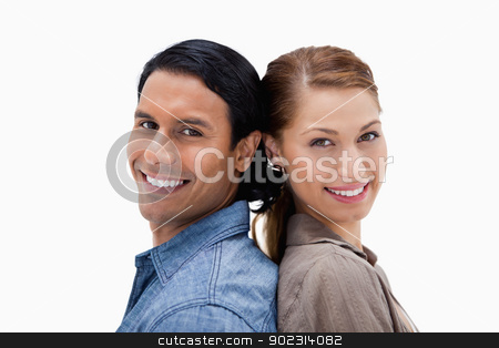 Side view of smiling couple standing back to back stock photo, Side view of smiling couple standing back to back against a white background by Wavebreak Media