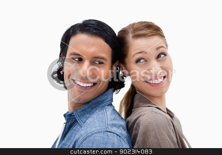 Side view of happy couple standing back to back stock photo, Side view of happy couple standing back to back against a white background by Wavebreak Media