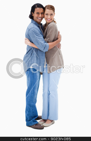 Side view of embracing happy couple stock photo, Side view of embracing happy couple against a white background by Wavebreak Media