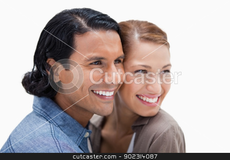 Close together standing couple looking to the right stock photo, Close together standing couple looking to the right against a white background by Wavebreak Media