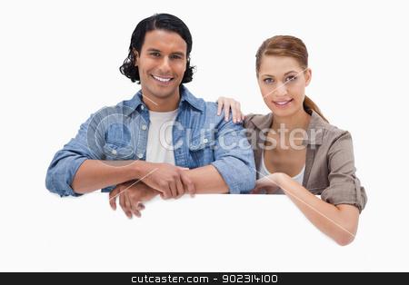 Couple leaning on blank wall stock photo, Couple leaning on blank wall against a white background by Wavebreak Media