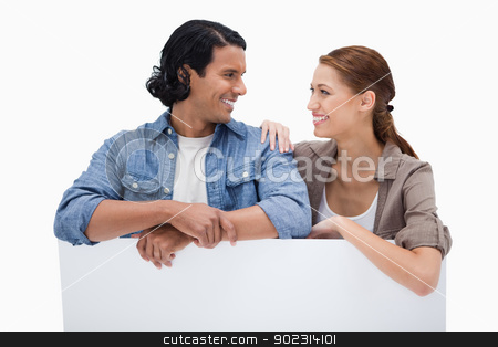 Smiling couple leaning on blank wall stock photo, Smiling couple leaning on blank wall against a white background by Wavebreak Media