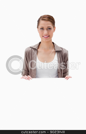 Smiling woman holding blank sign stock photo, Smiling woman holding blank sign against a white background by Wavebreak Media