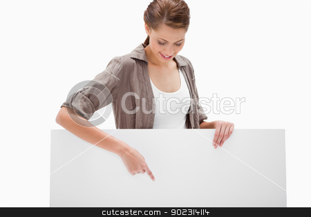 Woman pointing down at blank signboard stock photo, Woman pointing down at blank signboard against a white background by Wavebreak Media