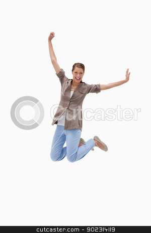 Cheerful woman jumping stock photo, Cheerful woman jumping against a white background by Wavebreak Media