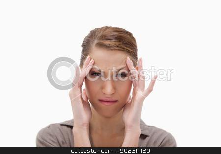 Sick woman rubbing her temples stock photo, Sick woman rubbing her temples against a white background by Wavebreak Media