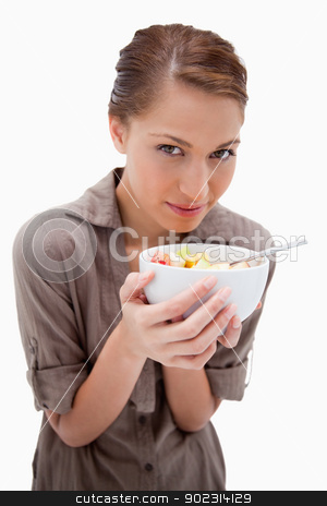 Woman with a bowl of fruit salad stock photo, Woman with a bowl of fruit salad against a white background by Wavebreak Media