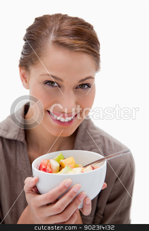 Smiling woman with bowl of fruit salad stock photo, Smiling woman with bowl of fruit salad against a white background by Wavebreak Media