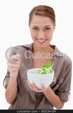 Woman with bowl of salad stock photo, Woman with bowl of salad against a white background by Wavebreak Media