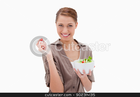 Woman with bowl of salad and small tomato in her fingers stock photo, Woman with bowl of salad and small tomato in her fingers against a white background by Wavebreak Media