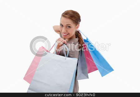 Side view of smiling woman with shopping bags stock photo, Side view of smiling woman with shopping bags against a white background by Wavebreak Media