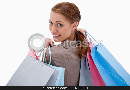Back view of smiling woman with shopping bags stock photo, Back view of smiling woman with shopping bags against a white background by Wavebreak Media